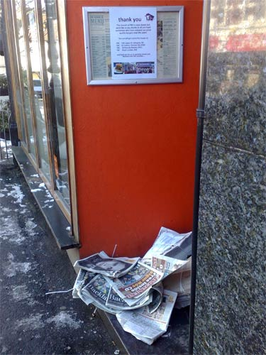 Newspapers piling up in the doorway